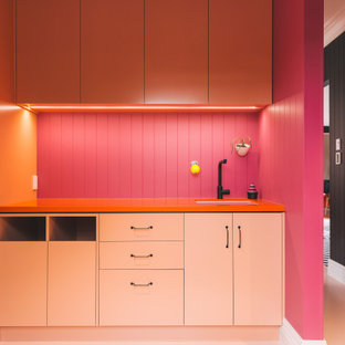 Inspiration for an eclectic galley painted wood floor, pink floor, shiplap ceiling and wainscoting laundry room remodel in Other with an undermount sink, raised-panel cabinets, orange cabinets, laminate countertops, pink backsplash, wood backsplash, pink walls, a stacked washer/dryer and orange countertops