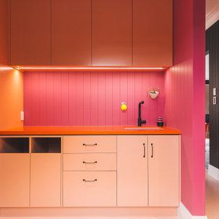 Пример оригинального дизайна: параллельная прачечная в стиле фьюжн с врезной раковиной, фасадами с выступающей филенкой, оранжевыми фасадами, столешницей из ламината, розовым фартуком, фартуком из дерева, розовыми стенами, деревянным полом, с сушильной машиной на стиральной машине, розовым полом, оранжевой столешницей, потолком из вагонки и панелями на стенах