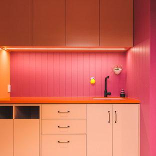 Идея дизайна: параллельная прачечная в современном стиле с врезной раковиной, фасадами с выступающей филенкой, оранжевыми фасадами, столешницей из ламината, розовым фартуком, фартуком из дерева, розовыми стенами, деревянным полом, с сушильной машиной на стиральной машине, розовым полом, оранжевой столешницей, потолком из вагонки и панелями на стенах