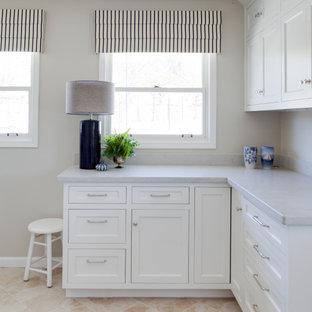 Idee per una sala lavanderia tradizionale di medie dimensioni con ante a filo, ante bianche, top in quarzo composito, pareti beige, pavimento in legno massello medio, lavatrice e asciugatrice affiancate, pavimento giallo e top bianco