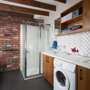 Utility room - mid-sized eclectic ceramic tile, gray floor, exposed beam and brick wall utility room idea in Other with a single-bowl sink, medium tone wood cabinets, white backsplash, subway tile backsplash and white countertops