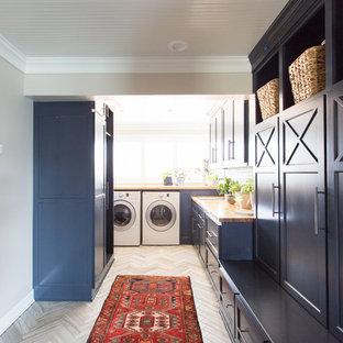 Ispirazione per una lavanderia multiuso stile marino di medie dimensioni con ante blu, top in legno, pareti grigie, lavatrice e asciugatrice affiancate e pavimento grigio