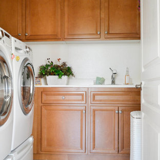Inspiration for a small mediterranean l-shaped dedicated laundry room in Los Angeles with a single-bowl sink, medium wood cabinets, white walls, travertine floors and a side-by-side washer and dryer.