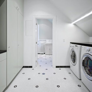 Design ideas for a medium sized scandinavian galley separated utility room in Toronto with flat-panel cabinets, grey cabinets, engineered stone countertops, white walls, a side by side washer and dryer, porcelain flooring, white floors and black worktops.