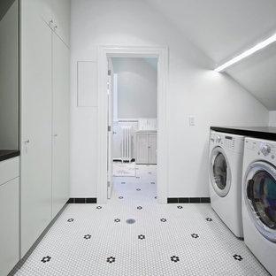 Idee per una sala lavanderia scandinava di medie dimensioni con ante lisce, ante grigie, top in quarzo composito, pareti bianche, lavatrice e asciugatrice affiancate, pavimento in gres porcellanato, pavimento bianco e top nero