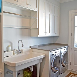 Inredning av ett klassiskt mellanstort grovkök, med en allbänk, skåp i shakerstil, vita skåp, bänkskiva i koppar, grå väggar, kalkstensgolv och en tvättmaskin och torktumlare bredvid varandra