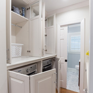 This is an example of a small transitional single-wall laundry cupboard in Charlotte with raised-panel cabinets, white cabinets, quartzite benchtops, white walls, medium hardwood floors, a concealed washer and dryer and brown floor.