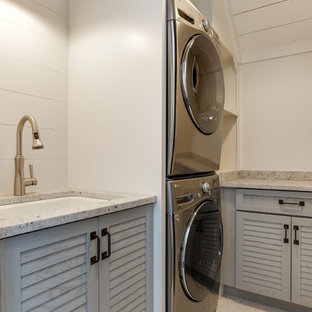 Inspiration for a small country dedicated laundry room in Raleigh with an undermount sink, louvered cabinets, grey cabinets, quartz benchtops, white walls, ceramic floors, a stacked washer and dryer, white floor and white benchtop.