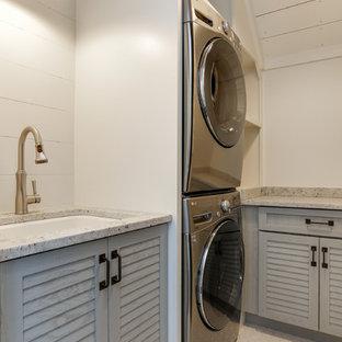 Immagine di una piccola sala lavanderia country con lavello sottopiano, ante a persiana, ante grigie, top in quarzo composito, pareti bianche, pavimento con piastrelle in ceramica, lavatrice e asciugatrice a colonna, pavimento bianco e top bianco