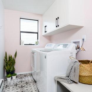Bild på en liten funkis grå linjär grått tvättstuga enbart för tvätt, med släta luckor, vita skåp, bänkskiva i kvarts, rosa väggar, klinkergolv i keramik, en tvättmaskin och torktumlare bredvid varandra och flerfärgat golv