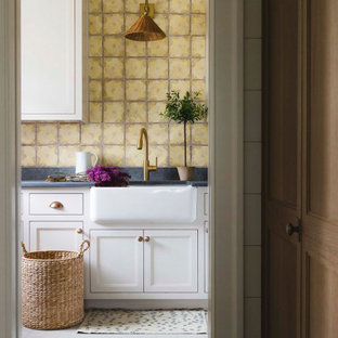 Laundry room - coastal laundry room idea in Chicago with a farmhouse sink, recessed-panel cabinets, white cabinets and black countertops