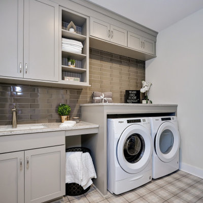 Utility room - traditional single-wall multicolored floor utility room idea in Other with an undermount sink, shaker cabinets, gray cabinets, beige walls, a side-by-side washer/dryer and gray countertops