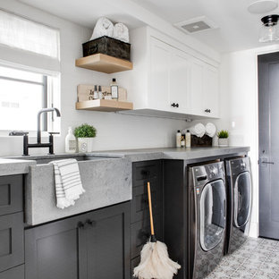 Inspiration for a coastal single-wall multicolored floor dedicated laundry room remodel in Los Angeles with a farmhouse sink, shaker cabinets, gray cabinets, white walls, a side-by-side washer/dryer and gray countertops