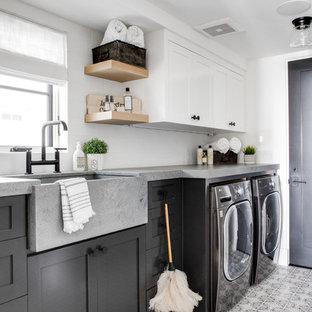 Idéer för en maritim grå linjär tvättstuga enbart för tvätt, med en rustik diskho, skåp i shakerstil, grå skåp, vita väggar, en tvättmaskin och torktumlare bredvid varandra och flerfärgat golv
