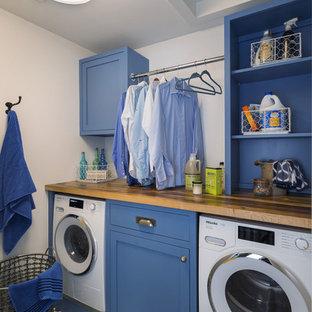 Idee per una piccola lavanderia multiuso country con ante a filo, ante blu, top in legno, pareti bianche, pavimento in gres porcellanato, lavasciuga, pavimento blu e top marrone