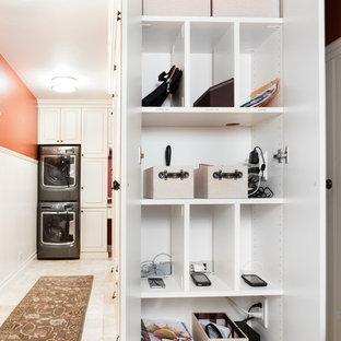 Esempio di una piccola lavanderia multiuso tradizionale con ante bianche, top in laminato, pareti arancioni, pavimento con piastrelle in ceramica, lavatrice e asciugatrice a colonna e ante con bugna sagomata