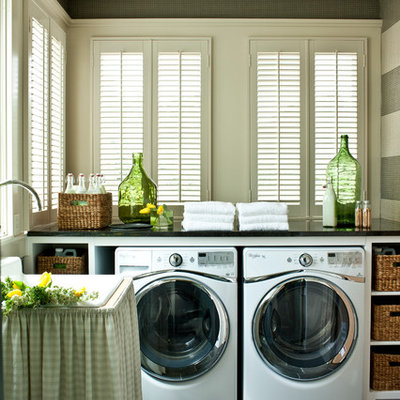 Inspiration for a large cottage slate floor laundry room remodel in Nashville with white cabinets, onyx countertops, a side-by-side washer/dryer, open cabinets, black countertops, a drop-in sink and gray walls