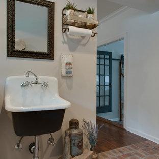 Inredning av ett lantligt litet svart svart grovkök, med en rustik diskho, skåp i shakerstil, bruna skåp, granitbänkskiva, grå väggar, tegelgolv, en tvättmaskin och torktumlare bredvid varandra och flerfärgat golv