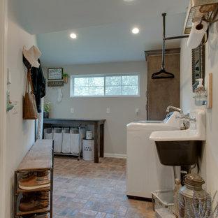 Inspiration för små lantliga svart grovkök, med en rustik diskho, skåp i shakerstil, bruna skåp, granitbänkskiva, grå väggar, tegelgolv, en tvättmaskin och torktumlare bredvid varandra och flerfärgat golv