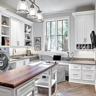 Inspiration for a mid-sized transitional utility room in Nashville with an undermount sink, white cabinets, white walls, light hardwood floors, open cabinets, limestone benchtops, a side-by-side washer and dryer, brown floor and brown benchtop.