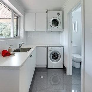 Idéer för en mellanstor modern vita l-formad tvättstuga enbart för tvätt, med en enkel diskho, vita skåp, laminatbänkskiva, vita väggar, klinkergolv i porslin, en tvättpelare, släta luckor och grått golv