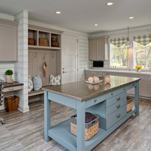 Inspiration for a large beach style utility room in Minneapolis with quartz benchtops, laminate floors, a side-by-side washer and dryer, brown floor, a single-bowl sink, shaker cabinets, brown cabinets, multi-coloured walls, white benchtop and wallpaper.