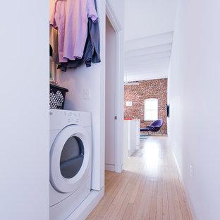Exempel på en nordisk liten tvättstuga, med vita väggar, ljust trägolv och en tvättmaskin och torktumlare bredvid varandra