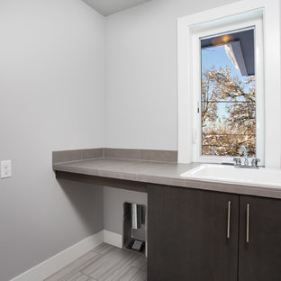 Mid-sized minimalist single-wall ceramic tile and gray floor utility room photo in Portland with a drop-in sink, flat-panel cabinets, dark wood cabinets, tile countertops, gray walls and a side-by-side washer/dryer
