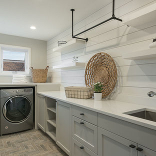 Dedicated laundry room - mid-sized contemporary l-shaped brick floor and red floor dedicated laundry room idea in Seattle with an undermount sink, shaker cabinets, gray cabinets, solid surface countertops, white walls and a side-by-side washer/dryer