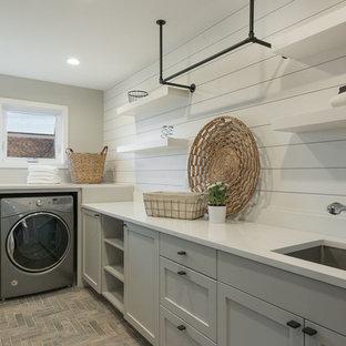 シアトルの中サイズのコンテンポラリースタイルのおしゃれな洗濯室 (アンダーカウンターシンク、シェーカースタイル扉のキャビネット、グレーのキャビネット、人工大理石カウンター、白い壁、レンガの床、左右配置の洗濯機・乾燥機、赤い床) の写真