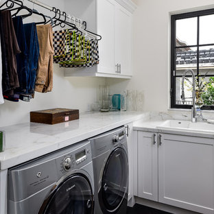 Example of a small transitional l-shaped dark wood floor and brown floor dedicated laundry room design in Miami with a drop-in sink, shaker cabinets, white cabinets, marble countertops, white walls and white countertops