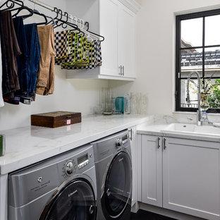 Idéer för att renovera en liten vintage vita l-formad vitt tvättstuga enbart för tvätt, med en nedsänkt diskho, skåp i shakerstil, vita skåp, marmorbänkskiva, vita väggar, en tvättmaskin och torktumlare bredvid varandra, mörkt trägolv och brunt golv