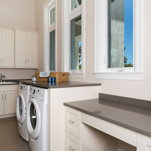 Inspiration för ett mellanstort tropiskt l-format grovkök, med luckor med infälld panel, vita skåp, bänkskiva i kvarts, en tvättmaskin och torktumlare bredvid varandra, en nedsänkt diskho, vita väggar och klinkergolv i porslin