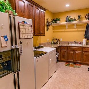 Exempel på en stor flerfärgade l-formad flerfärgat tvättstuga enbart för tvätt, med luckor med upphöjd panel, bruna skåp, granitbänkskiva, gula väggar, en tvättmaskin och torktumlare bredvid varandra, beiget golv och en nedsänkt diskho