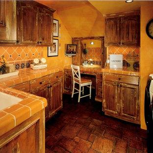 Cette photo montre une buanderie méditerranéenne avec un évier encastré, un placard avec porte à panneau surélevé, des portes de placard en bois vieilli, un plan de travail en carrelage, un sol en carreau de terre cuite, des machines côte à côte, un plan de travail orange et un mur orange.