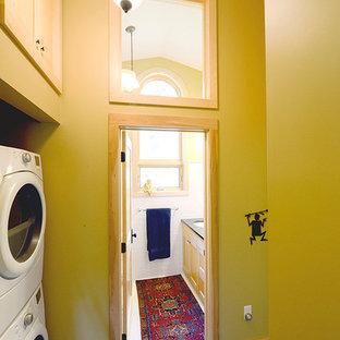 Immagine di una lavanderia multiuso classica con ante in stile shaker, ante in legno chiaro, pareti verdi e lavatrice e asciugatrice a colonna