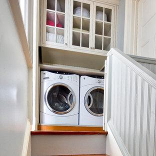 Bild på en liten vintage vita linjär vitt liten tvättstuga, med luckor med profilerade fronter, vita skåp, träbänkskiva, blå väggar, mellanmörkt trägolv och en tvättmaskin och torktumlare bredvid varandra