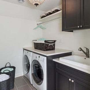 Inspiration för en mellanstor vintage linjär tvättstuga enbart för tvätt, med en nedsänkt diskho, svarta skåp, laminatbänkskiva, vita väggar, klinkergolv i porslin, en tvättmaskin och torktumlare bredvid varandra och skåp i shakerstil
