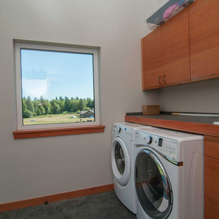 Small trendy single-wall concrete floor dedicated laundry room photo in Seattle with a drop-in sink, flat-panel cabinets, medium tone wood cabinets, laminate countertops, gray walls and a side-by-side washer/dryer
