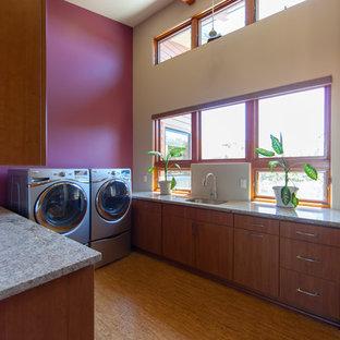 Modern inredning av ett stort u-format grovkök, med en undermonterad diskho, släta luckor, skåp i mellenmörkt trä, granitbänkskiva, korkgolv, en tvättmaskin och torktumlare bredvid varandra och rosa väggar