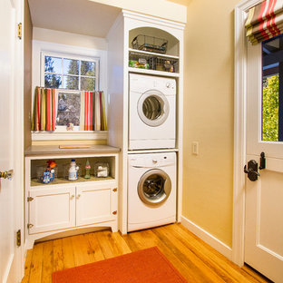 Mid-sized elegant single-wall light wood floor and beige floor dedicated laundry room photo in Sacramento with white cabinets, shaker cabinets, quartz countertops, beige walls, a stacked washer/dryer and beige countertops