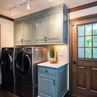 Immagine di una sala lavanderia mediterranea di medie dimensioni con ante con bugna sagomata, ante verdi, top in quarzite, pareti beige, parquet scuro, lavatrice e asciugatrice affiancate e pavimento marrone
