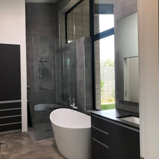 Mid-sized contemporary galley dedicated laundry room in Phoenix with an undermount sink, flat-panel cabinets, grey cabinets, quartzite benchtops, grey splashback, subway tile splashback, white walls, concrete floors, a stacked washer and dryer, beige floor, grey benchtop and wood.