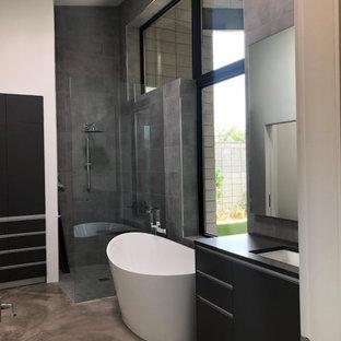 Exempel på en mellanstor modern grå parallell grått tvättstuga enbart för tvätt, med en undermonterad diskho, släta luckor, grå skåp, bänkskiva i kvartsit, grått stänkskydd, stänkskydd i tunnelbanekakel, vita väggar, betonggolv, en tvättpelare och beiget golv
