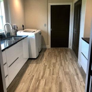 Immagine di una lavanderia moderna con lavello sottopiano, ante lisce, ante bianche, top in quarzite, pareti marroni, pavimento in gres porcellanato, lavatrice e asciugatrice affiancate, pavimento marrone e top marrone