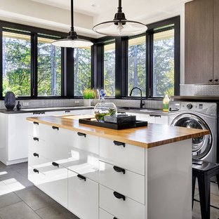 This is an example of a large contemporary u-shaped utility room in Portland with a built-in sink, flat-panel cabinets, white cabinets, wood worktops, grey walls, porcelain flooring, a side by side washer and dryer and grey floors.