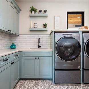 Mid-sized trendy l-shaped ceramic tile and multicolored floor dedicated laundry room photo in San Diego with an undermount sink, recessed-panel cabinets, blue cabinets, beige walls, a side-by-side washer/dryer, beige countertops and quartz countertops