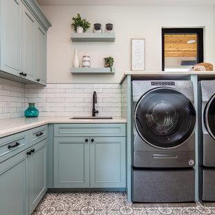 サンディエゴの中サイズのコンテンポラリースタイルのおしゃれな洗濯室 (アンダーカウンターシンク、落し込みパネル扉のキャビネット、青いキャビネット、ベージュの壁、左右配置の洗濯機・乾燥機、ベージュのキッチンカウンター、クオーツストーンカウンター、セラミックタイルの床、マルチカラーの床) の写真