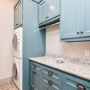 Immagine di una sala lavanderia mediterranea di medie dimensioni con ante a filo, top in superficie solida, pareti bianche, pavimento in mattoni, pavimento multicolore, top verde, ante blu e lavatrice e asciugatrice a colonna