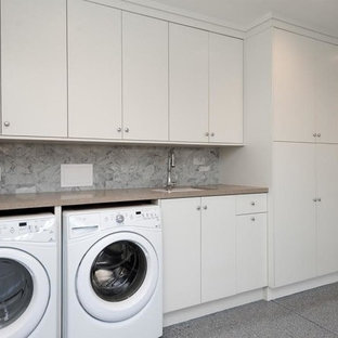 Large classic single-wall separated utility room in Los Angeles with a built-in sink, flat-panel cabinets, white cabinets, laminate countertops, white walls, ceramic flooring, a side by side washer and dryer and grey floors.